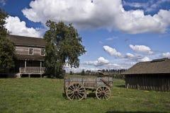 Gammal lantbrukarhem och vagn Royaltyfri Fotografi