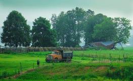 Gammal lantgård och övergiven dumper Arkivbild