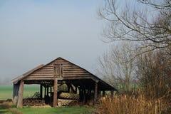 Gammal lantgårdbyggnad mot en blå/vit himmel Royaltyfri Foto