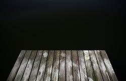 Gammal lantlig grungepirbro på wi för en sjö för blått vatten för mörk svart royaltyfria bilder