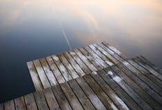 Gammal lantlig grungepirbro på wi för en sjö för blått vatten för mörk svart royaltyfri foto