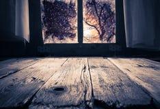 Gammal lantlig inre fönstertabell som förbiser vinterafton Arkivbild