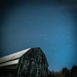 Gammal lantlig ladugård med den Karlavagnen- och Pole stjärnan i vinter royaltyfri bild