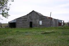 Gammal lantlig träladugård i fält Arkivbild