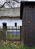Gammal lantlig trätoalett och historiskt hus med att halmtäcka taket Royaltyfria Bilder