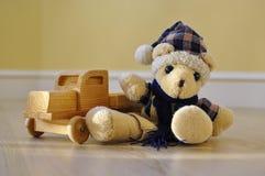 Gammal leksakbjörn med en träbil Arkivfoton
