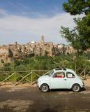 Gammal liten bil, grön dal och medeltida stad, Italien Arkivfoto