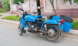 Gammal ljus blå motorcykel med sidobilen som parkeras i kubansk gata Arkivfoto