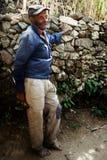 gammal lokal bonde som har en vila i skuggan framme av ett stenstaket royaltyfri fotografi