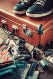 Gammal loppresväska, gymnastikskor, kläder, översikt och kamera arkivbilder