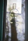 Gammal lykta till och med reflekterande fönster Arkivfoton