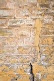 Gammal målad tegelstenvägg med en spricka royaltyfri fotografi