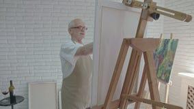 Gammal målare som talar i atelieren, teckning som ser kameran stock video