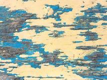 Gammal målarfärgblått och guling färgar på en smutsig träyttersida Arkivfoton