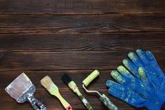 Gammal målarfärgborstar och spackel, blåa byggnadshandskar Arkivbilder