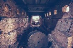 Gammal mörk kuslig underjordisk tegelstentunnel eller korridor eller avklopprörledning på den övergav förstörda industriella fabr royaltyfri foto