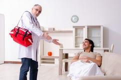 Gammal manlig doktor som besöker den unga manliga patienten arkivbild