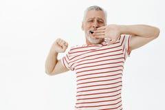 Gammal manlig lat pensionärkänsla i dag Bekymmerslös avkopplad stilig hög man med skägget och grått hår i randig t-skjorta royaltyfria foton