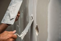 Gammal manuell arbetare med väggen som rappar hjälpmedel som renoverar huset Arkivbild