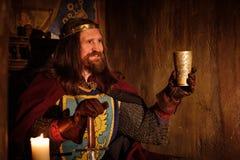 Gammal medeltida konung med bägaren av vin på biskopsstolen i forntida slottinre royaltyfri bild