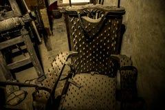 Gammal medeltida tortyrkammare med stol och hjälpmedel Fotografering för Bildbyråer