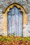 Gammal medeltida trädörr med den dekorativa bågen och Autumn Leaves arkivfoton