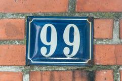 Gammal metall nummer 99 nittionio för blått för tappninghusadress på tegelstenfasaden av den yttre väggen för bostads- byggnad på Royaltyfri Bild