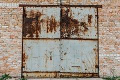 Gammal metalldörr från garaget rostigt Gamla röda tegelstenar för garage lodisar royaltyfri bild