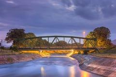 Gammal metallisk järnvägbro över silkeslent vatten under blå timme Royaltyfri Bild