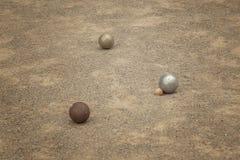 Gammal metallisk petanque klumpa ihop sig på botstenfält fotografering för bildbyråer