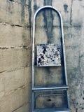 Gammal metallisk stege på väggen i gatan royaltyfria bilder
