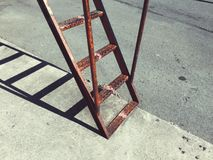 Gammal metallisk stege p? v?ggen i gatan royaltyfri foto