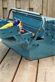 Gammal metalltoolbox med hjälpmedel, på en träträdgårds- tabell Royaltyfri Fotografi
