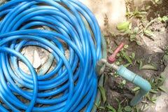 Gammal metallvattenkran och blått rubber rör som går från metallröret på jordningen arkivfoto