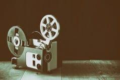 Gammal 8mm filmprojektor över trätabellen och texturerad bakgrund Royaltyfri Foto