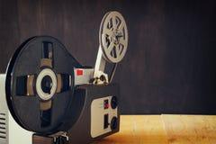 Gammal 8mm filmprojektor över trätabellen och texturerad bakgrund Royaltyfria Bilder