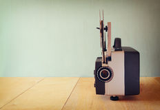 Gammal 8mm filmprojektor över trätabellen och texturerad bakgrund Arkivfoto