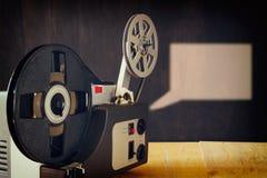 Gammal 8mm filmprojektor över trätabellen och texturerad bakgrund Royaltyfria Foton