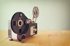 Gammal 8mm filmprojektor över trätabellen och texturerad bakgrund Royaltyfri Bild