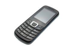 Gammal mobiltelefon som isoleras på en vit bakgrund, med den snabba banan Fotografering för Bildbyråer