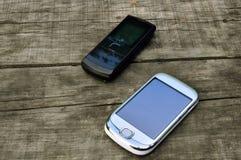 Gammal mobiltelefon som två ligger på den gamla trätabellen Arkivbild