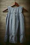 Gammal modeflickaklänning på en klädhängare Royaltyfri Foto