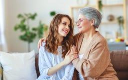 Gammal moder f?r lyckliga utvecklingar f?r familj tv? och vuxen dotter fotografering för bildbyråer