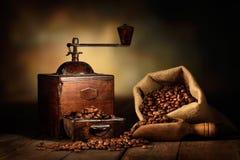 Gammal molar med jutepåse- och kaffebönor fotografering för bildbyråer