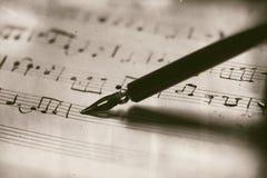 Gammal musikalisk ställning med reservoarpennan Arkivfoto