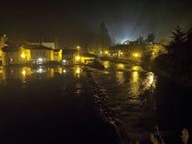 Gammal by nära floden i natten Arkivfoto
