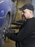 Gammal nöjd mekaniker som fixar den gammala bilen Arkivfoto