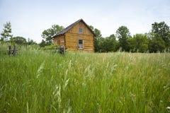 Gammal nybyggares kabin som beskådas från gräs- fält Arkivbild