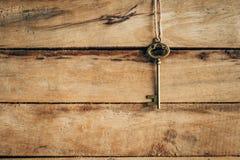Gammal nyckel- tappning som hänger på träbakgrund Royaltyfri Foto