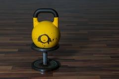 Gammal och använd hantel för idrottshallsvartmetall med gul kettlebell på ett trägolv Arkivfoto